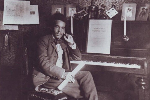 A photograph of Samuel Coleridge-Taylor sitting at his piano