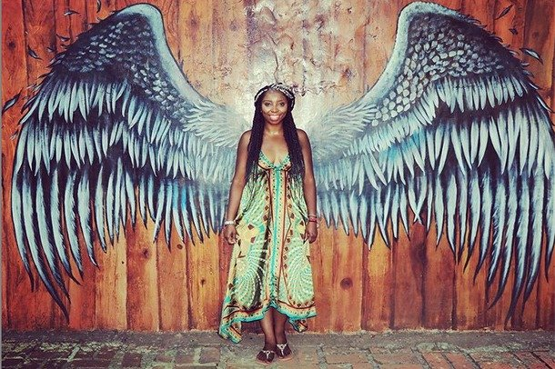 Tiik stands in front of a painting of outstretched wings