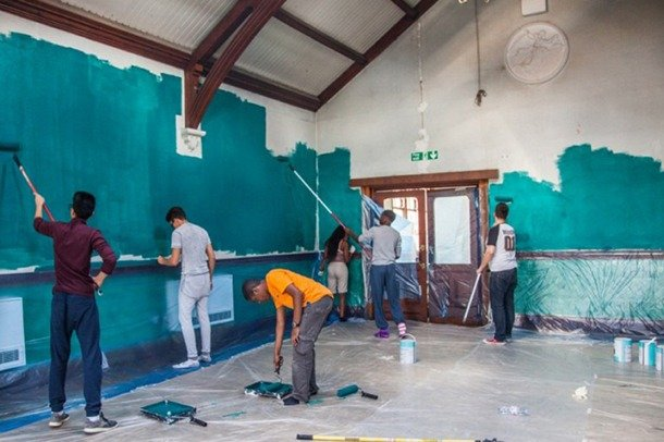 A group of young people paint walls.